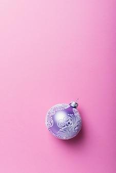 Bola de navidad violeta sobre fondo rosa, concepto de navidad. vista de arriba hacia abajo con espacio para copiar texto