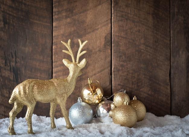 Bola navideña dorada plateada y decoración de renos con madera