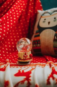 Bola de nieve globo sobre manta roja y almohada