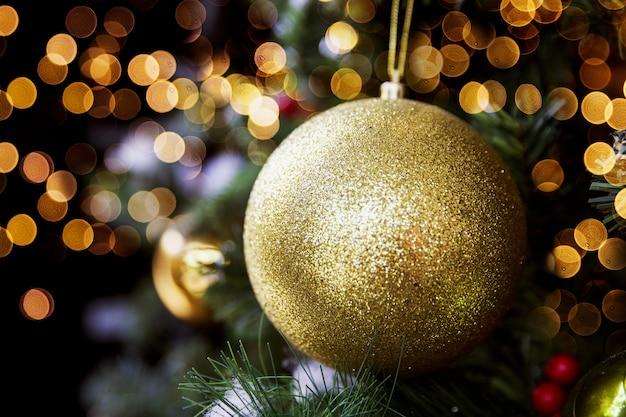 Bola de oro brillante brillante en el árbol de navidad con luces borrosas. concepto de vacaciones. de cerca.