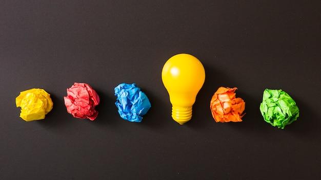 Bola de papel arrugada colorida con el bulbo de la luz ámbar contra fondo negro