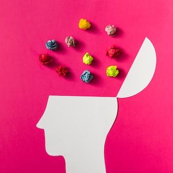 Bola de papel arrugada colorida sobre la cabeza humana blanca cortada en fondo rosado