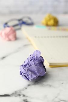 Bola de papel arrugado y bloc de notas en la mesa de madera