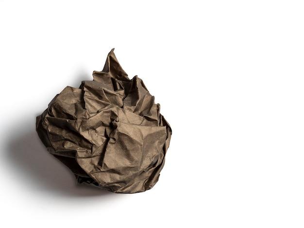 Una bola de papel marrón arrugado aislado sobre un fondo claro.