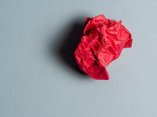 Una bola de papel rojo arrugado sobre un fondo claro.