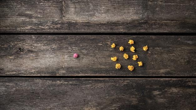 Bola de papel rosa y arrugada que sobresalía de la multitud de las otras, amarillas.