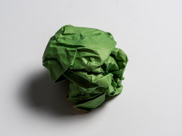 Una bola de papel verde arrugado sobre un fondo claro.
