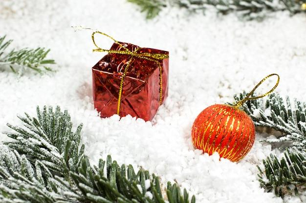 Bola roja y caja de regalo con ramas de abeto en la nieve.