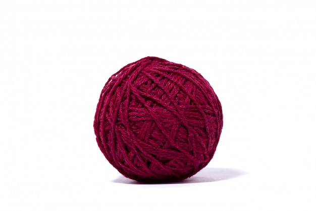 Bola roja oscura del hilo de lana, pared blanca aislada.