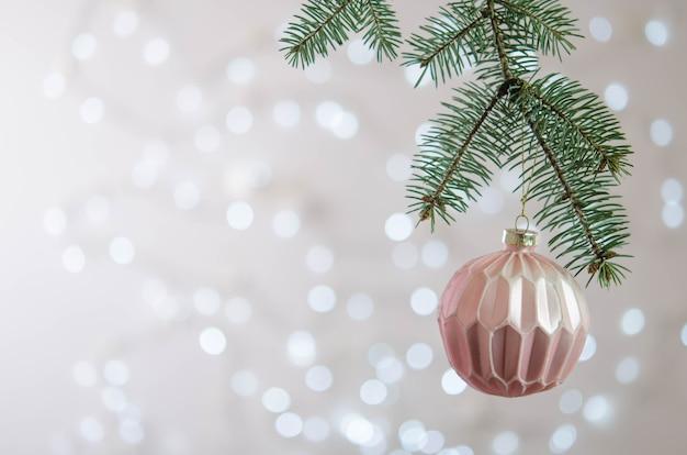 Una bola rosa cuelga de la rama de un árbol de navidad. bokeh. decoración navideña
