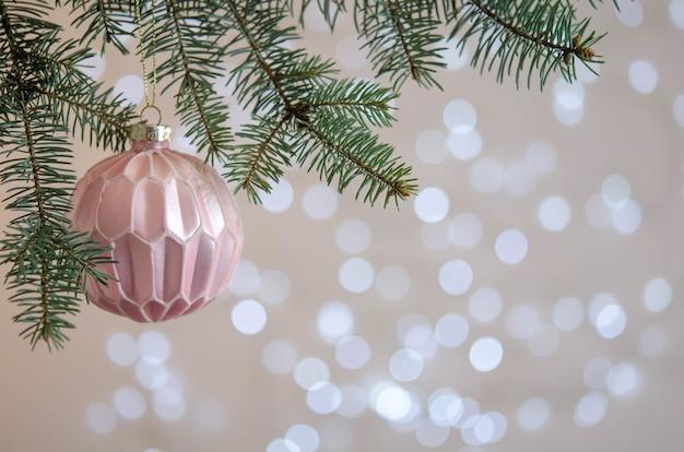 Una bola rosa cuelga de la rama de un árbol de navidad