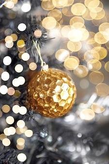 Bola de textura brillante dorada en árbol de navidad con luces borrosas. concepto de vacaciones. de cerca.