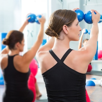 Bola tonificante azul en la clase de pilates de mujeres vista trasera