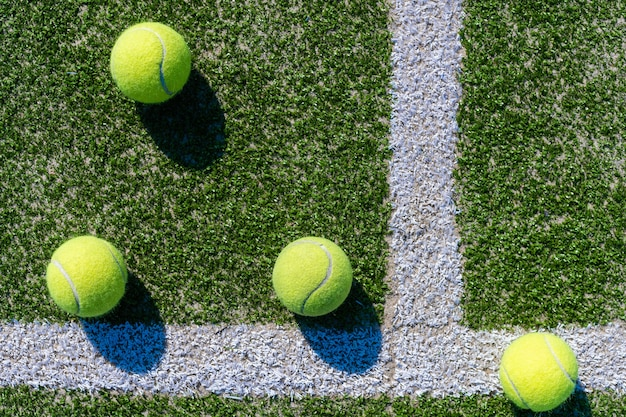 Bola verde cayendo en el piso casi líneas blancas de la cancha de tenis al aire libre en un parque público