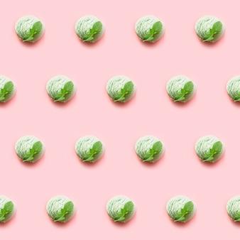 Una bola verde del helado del té del pistacho o del matcha con la menta en fondo rosado