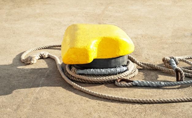 Bolardo de amarre metálico con cuerda anudada para transporte náutico en el puerto marítimo
