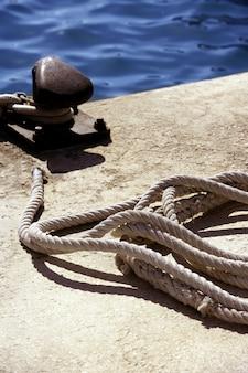 Bolardo de barco, cuerdas y nudos en puerto mediterraneo.