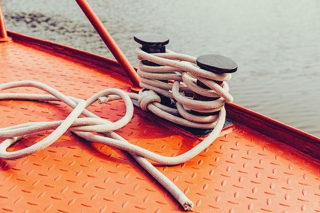 Bolardo y cuerda de amarre en la superficie metálica roja del barco