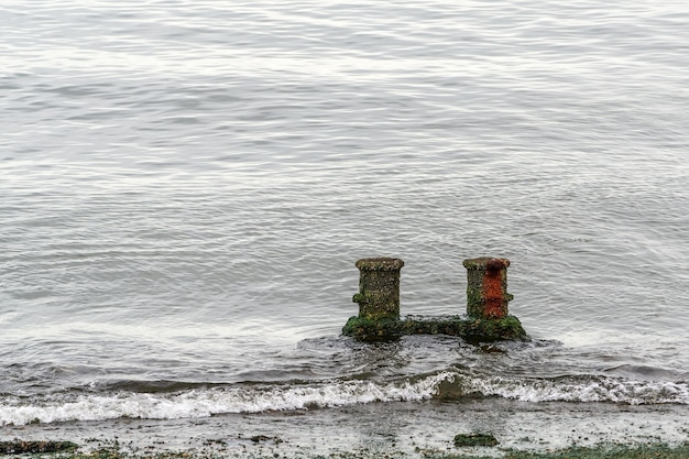 Bolardos oxidados viejos en la orilla