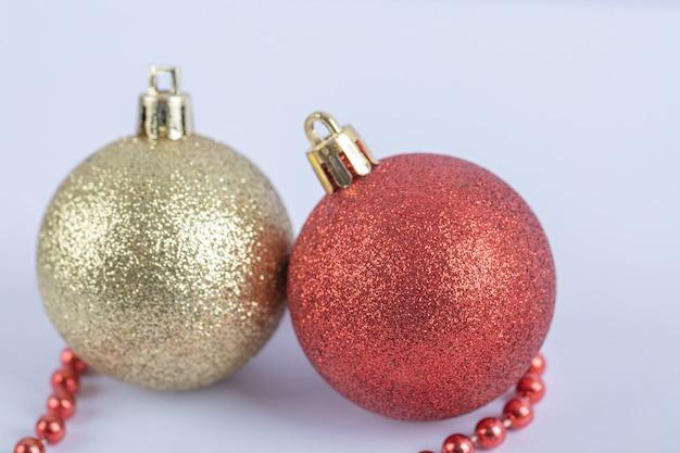Bolas de árbol de navidad con cadena de perlas rojas sobre el blanco
