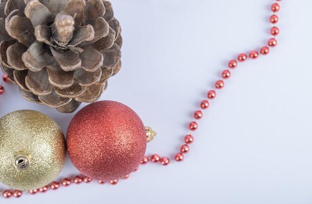 Bolas de árbol de navidad y conos de roble con cadena de perlas rojas sobre el blanco