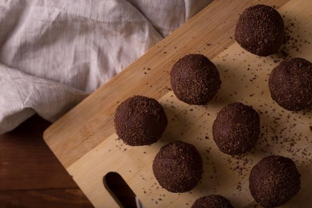Bolas de cacao, tortas de trufas de chocolate a bordo en la mesa de madera