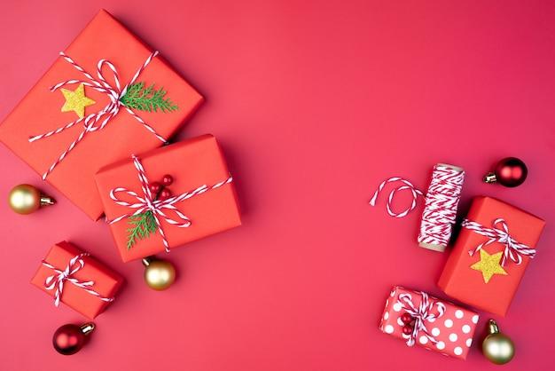 Bolas de la caja de regalo de la navidad, rojas y de oro en fondo rojo.