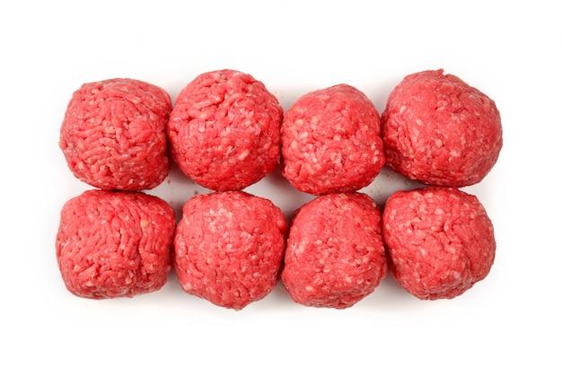 Bolas de carne cruda aisladas sobre fondo blanco.