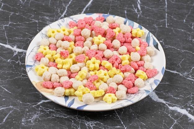 Bolas de cereales de colores en un plato blanco.