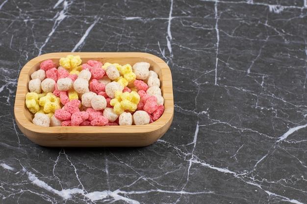 Bolas de cereales de colores sobre placa de madera. ilustración de alta calidad
