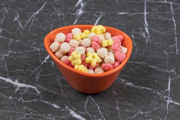 Bolas de cereales de colores en tazón de fuente naranja.