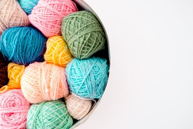 Bolas de colores de lana con agujas de tejer sobre fondo blanco, hobby y concepto de tiempo libre. hilos para tejer copyspace