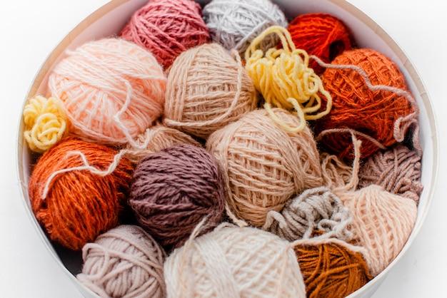 Bolas coloridas de lanas con las agujas que hacen punto en el fondo blanco, la afición y el concepto del tiempo libre. hilos para tejer