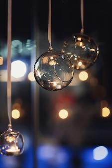 Bolas de cristal con velas colgadas antes de la ventana