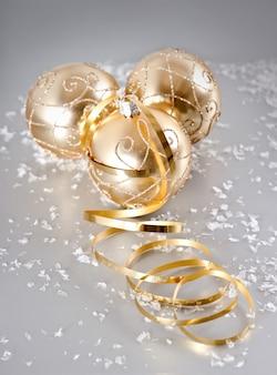Bolas doradas de navidad con decoración de nieve