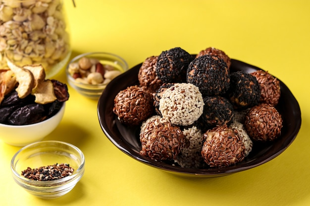 Bolas e ingredientes energéticos: nueces, avena y frutos secos en un plato de color amarillo,