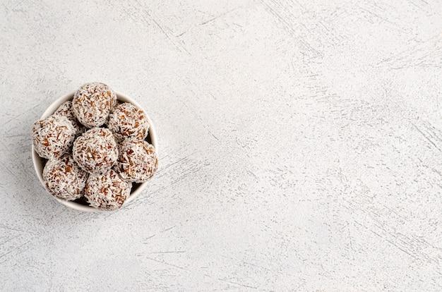 Bolas energéticas de dátiles, nueces, avena, espolvoreadas con coco en polvo closeup