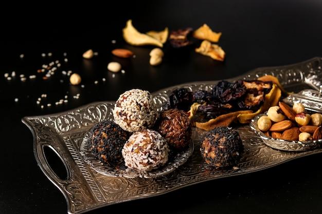 Bolas energéticas de nueces, avena y frutas secas en una bandeja de metal sobre una superficie oscura, orientación horizontal