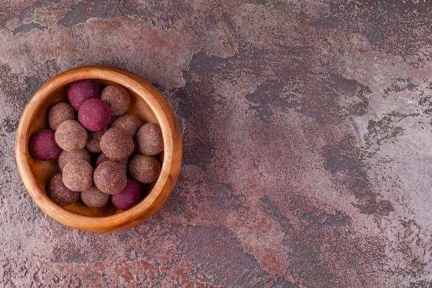 Bolas de energía de cacao vegano crudo casero en tazón de madera
