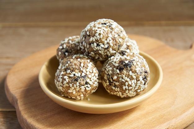 Bolas de energía cruda veganas saludables caseras con sésamo en tablero de madera cuttng.