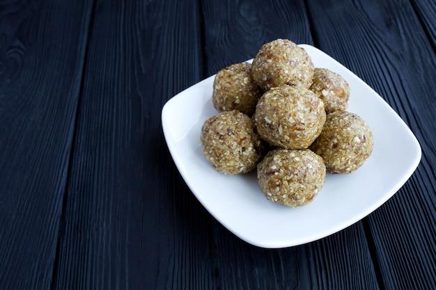 Bolas de energía con nueces, cereales de avena, dátiles y miel en el plato blanco sobre la mesa de madera negra. de cerca. copie el espacio.