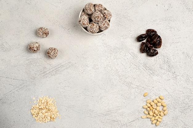 Bolas de energía en un plato blanco y fechas de ingredientes, avena, maní para su preparación, endecha plana, espacio de copia
