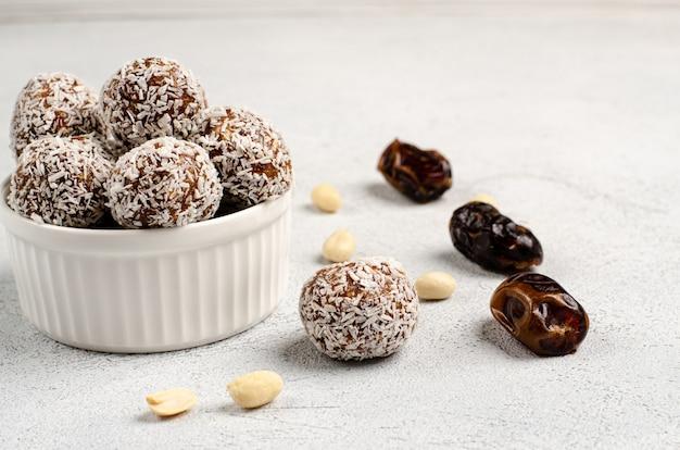 Bolas de energía en un plato blanco y fechas de ingredientes, nueces de maní para su preparación, endecha plana