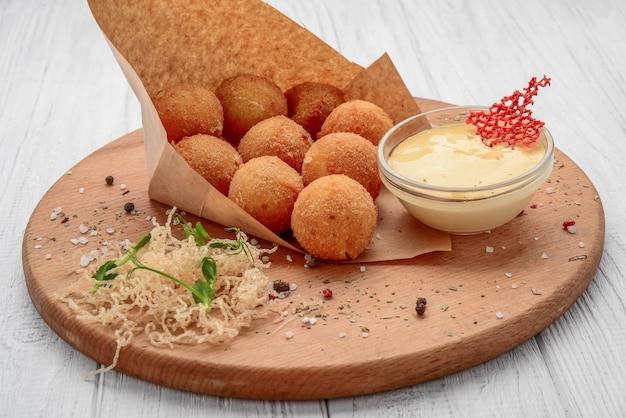 Bolas fritas de macarrones con queso servidas con salsa de tomate, enfoque selectivo