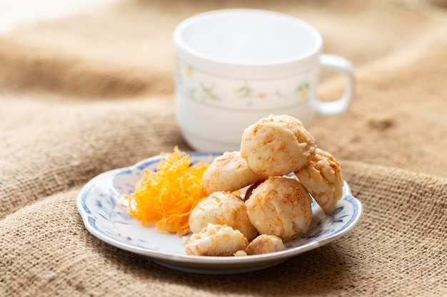 Bolas de galletas doradas con seda de huevos para la hora del té en la mañana en plato blanco