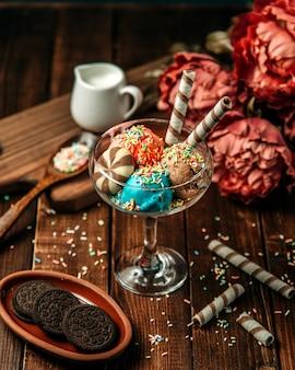 Bolas de helado cubiertas con galletas y dulces.