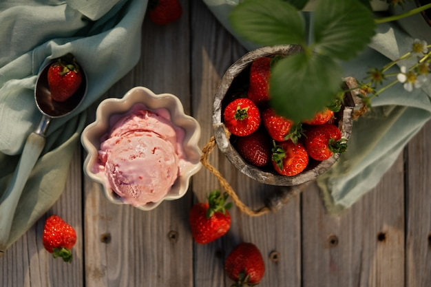 Bolas de helado de fresa con fresas frescas en hermosos tazones de helado