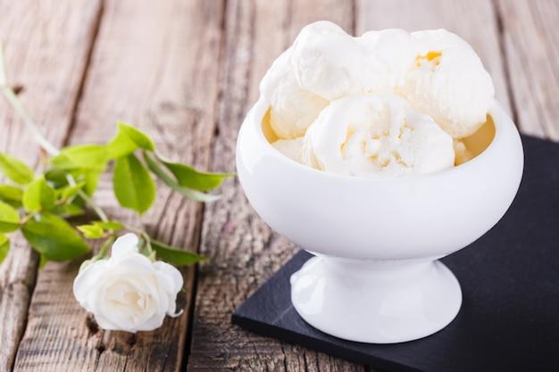 Bolas de helado en un recipiente cerca de una rosa blanca