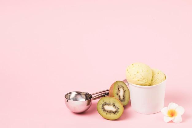 Bolas de helado en una taza cerca de kiwi con pala y flor