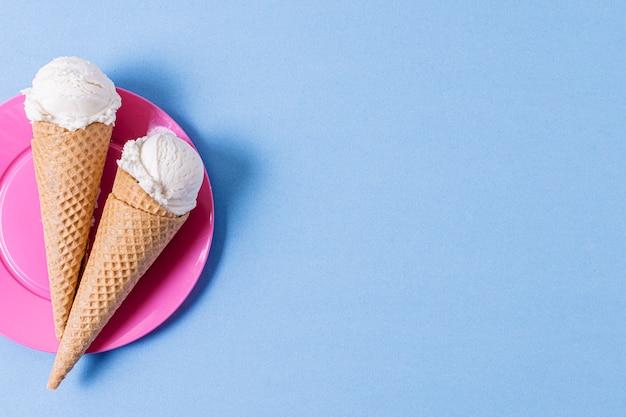 Bolas de helado de vainilla con conos y espacio de copia